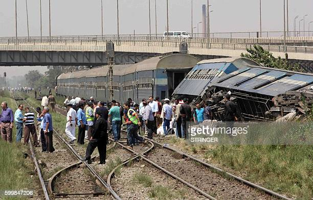 TOPSHOT Egyptians check the wreckage of a train after it derailed near the village of AlAyyat in Giza on the southern outskirts of the capital Cairo...