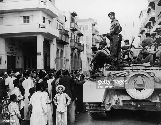 Egyptians crowd around a British tank in Port Said during the Suez Crisis 12th November 1956