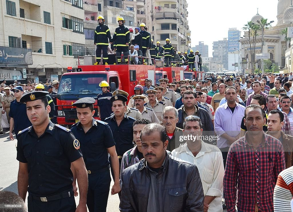 Egyptians escort firefighters vehicles with on their top the coffins of the three policemen that were killed during an attack against security forces on October 28, 2013 during their funeral procession in the Nile delta city of Mansura. Gunmen killed today the three policemen in Egypt, where attacks against security forces have been on the rise in the face of a bloody crackdown against Islamists, security officials said.