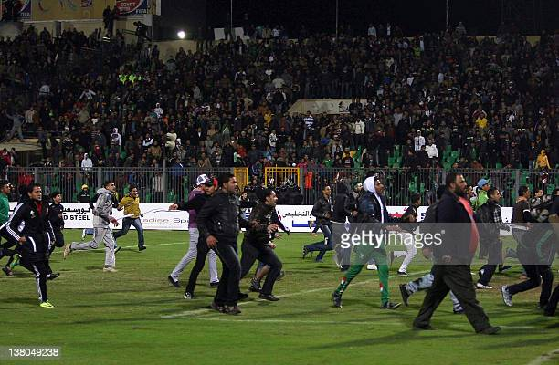 Egyptians football fans rush to the fiels during clashes that erupted after a football match between Egypt's AlAhly and AlMasry teams in Port Said...