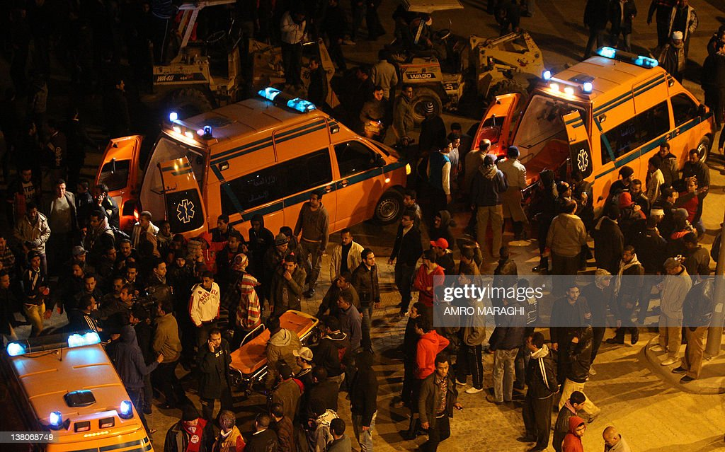 Egyptians gather around ambulances outside the train station in Cairo as they wait for the arrival of people who were wounded in clashes after a...