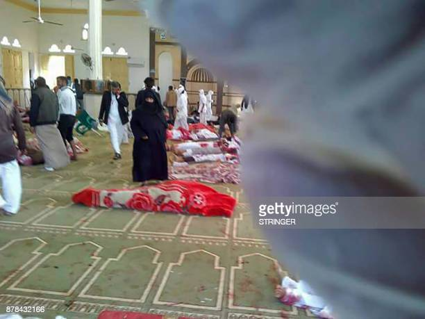Egyptians gather around bodies following a gun and bombing attack at the Rawda mosque roughly 40 kilometres west of the North Sinai capital of...
