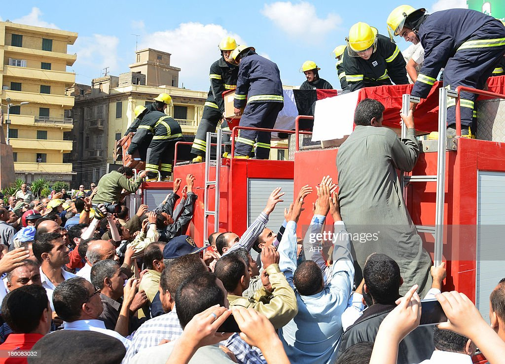 Egyptians gather around firefighters vehicles with on their top the coffins of the three policemen that were killed during an attack against security forces ahead of their funeral procession on October 28, 2013 in the Nile delta city of Mansura. Gunmen killed today the three policemen in Egypt, where attacks against security forces have been on the rise in the face of a bloody crackdown against Islamists, security officials said.