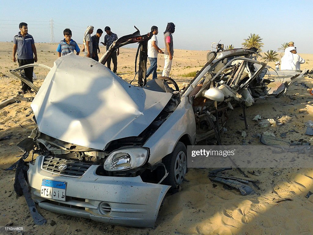 Egyptians gather near a damaged car bomb that detonated before reaching the intended target killing three passengers on July 24, 2013 in El-Arish in Egypt's Sinai peninsula. The bomb went off as the assailants entered the north Sinai town of El-Arish, where two soldiers were killed in separate shooting attacks earlier, said security officials.