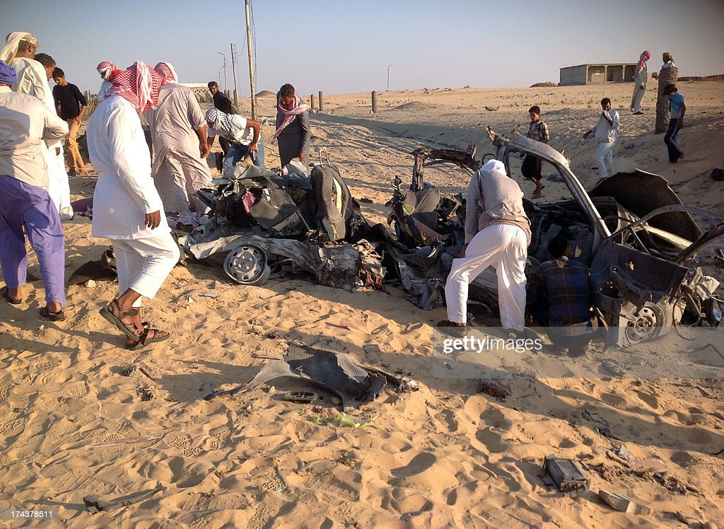 Egyptians gather near a damaged car bomb that exploded before reaching the intended target, killing three passengers on July 24, 2013 in El-Arish, in Egypt's Sinai peninsula. The bomb went off as the assailants entered the north Sinai town of El-Arish, where two soldiers were killed in separate shooting attacks earlier, said security officials.