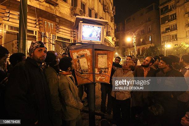 Egyptians gather to watch the AlJazeera satellite television station on a set placed on top of public telephone booths in Cairo's Tahrir Square...