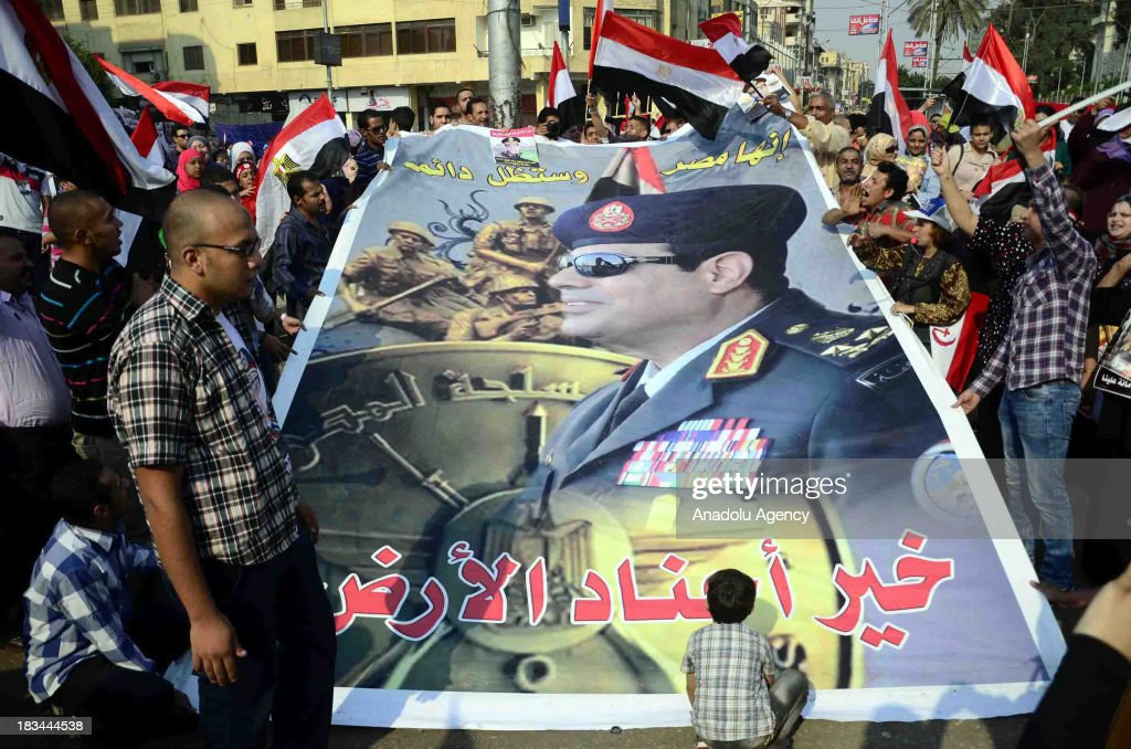 Egyptians hold a poster of General Abdel Fattah al-Sisi and wave national flags during the celebration marking the 40th anniversary of the 1973 victory over Israel around the Ittihadiya presidential palace on October 6, 2013 in Cairo, Egypt. Egypt celebrates the 40th anniversary of the 6th of October War victory against Israel for regaining the Sinai Peninsula.