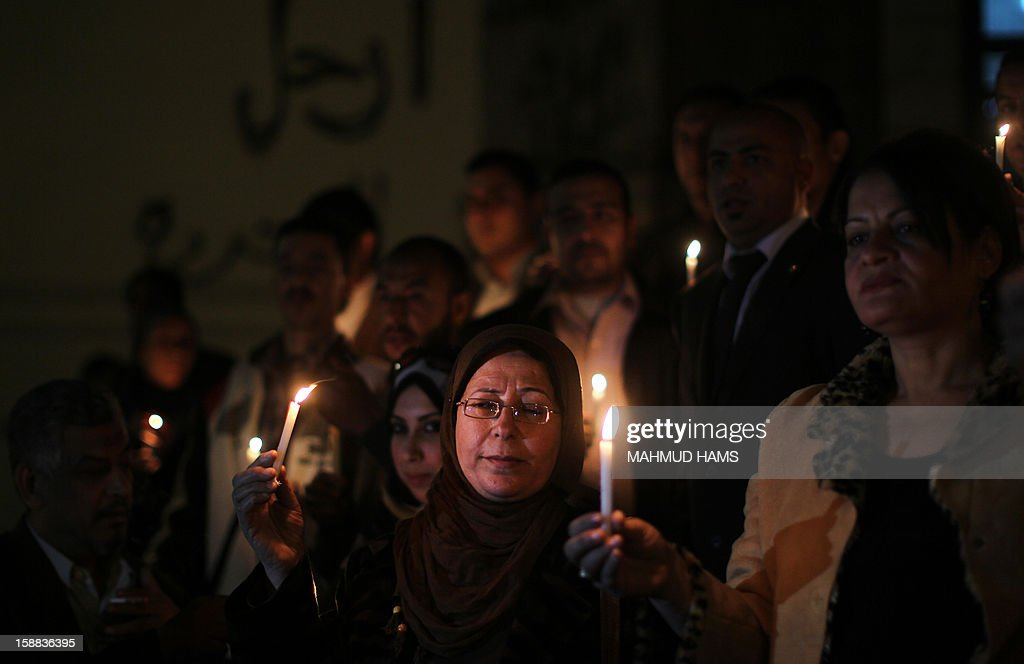 Egyptians hold candles at the entrance of the jounalist's sydicate in Cairo on December 31, 2012, during a rally to commemorate the anniversary of the car bomb attack on the Al-Qiddissine (The Saints) church in the port city of Alexandria on January 1, 2011. The attack killed at least 21 people, hitting Egypt's Christian community, the biggest in the Middle East.