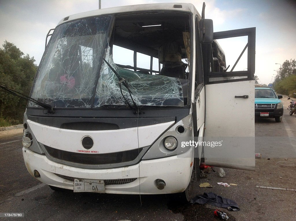 Egyptians inspect the site of an attack by militants on a bus carrying workers in the North Sinai town of Al-Arish, on July 15, 2013. The bus was targeted with a rocket-propelled grenade and left at least three people dead and 17 wounded, according to a security official.