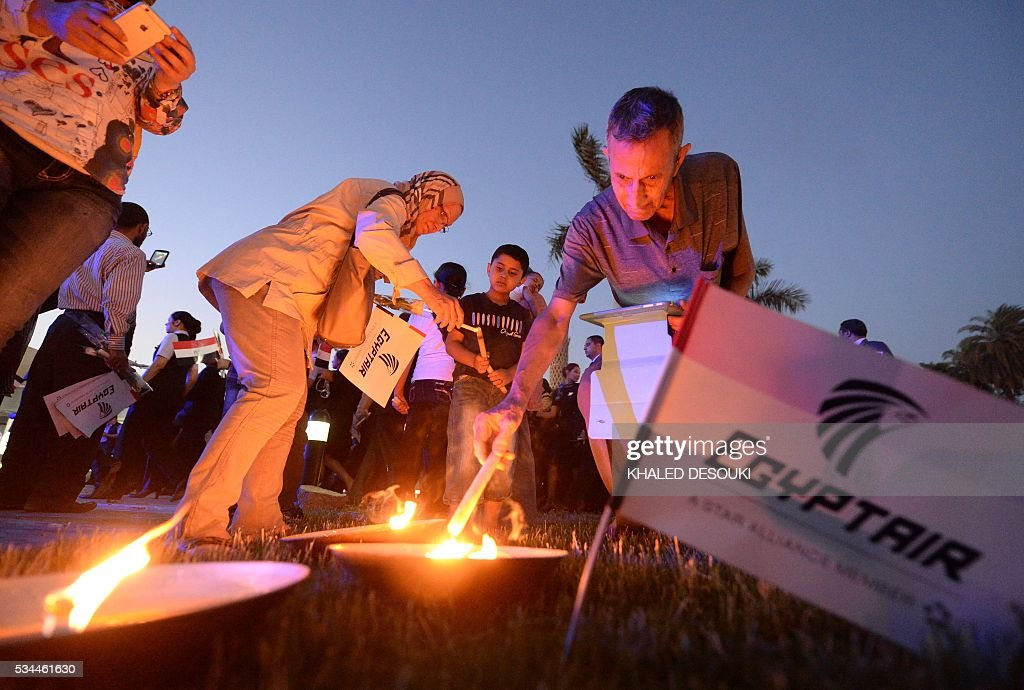 Egyptians light candles during a candlelight vigil for the 66 victims of the EgyptAir MS804 flight that crashed in the Mediterranean Sea, at the Cairo Opera House in the Egyptian capital on May 26, 2016. Investigators are still searching for the Airbus A320's two black boxes on the seabed as they seek answers as to why the aircraft came down early on May 19, with 66 people on board. DESOUKI