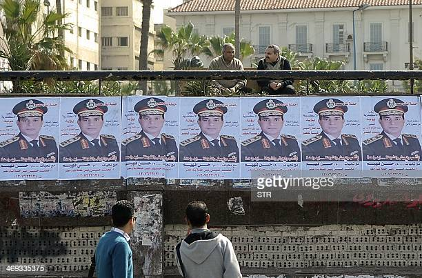 Egyptians look at a row of portraits of Egyptian army chief Abdel Fattah alSisi supporting him to run for presidency in the upcoming elections in...