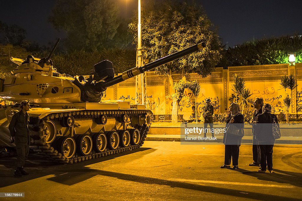 Egyptians look at a tank parked in front of the presidential palace on December 12, 2012 in Cairo, Egypt. Anti-Morsi protesters were quiet after continued demonstrations across Egypt against the country's draft constitution, rushed through parliament in an overnight session on November 29. The country's new draft constitution, passed by a constitutional assembly dominated by Islamists, will go to a referendum on December 15.