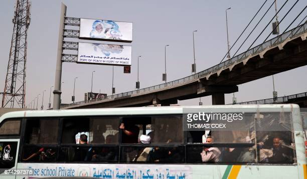 Egyptians look outside a public transportation bus in the capital Cairo with a billboard seen in the background depicting Pope Francis a few hours...