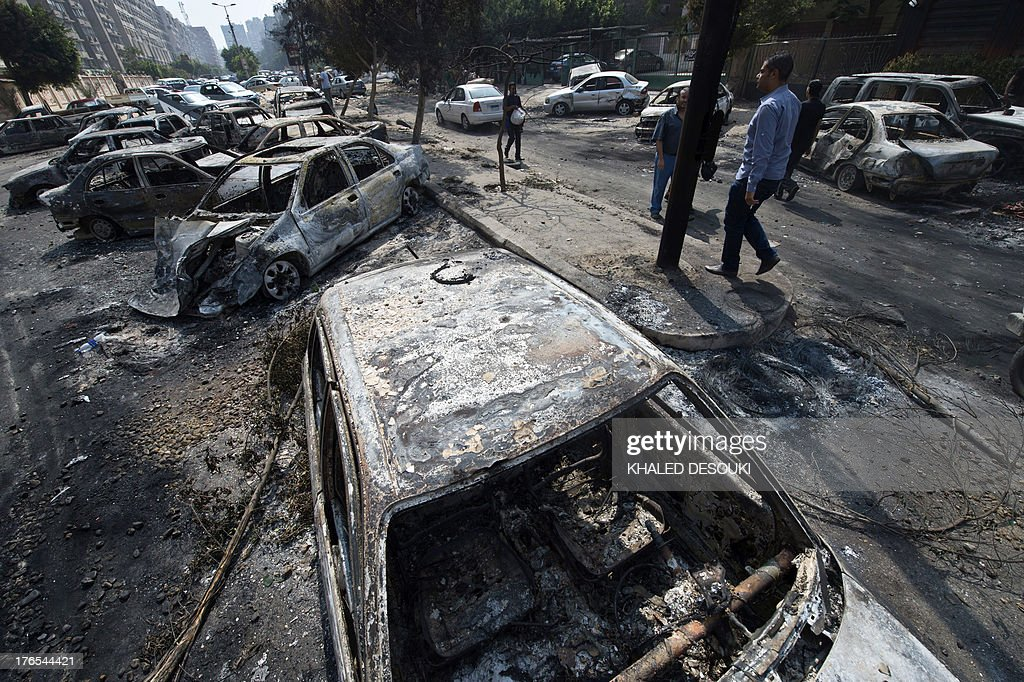 Egyptians pass by burnt vehicles outside the destroyed camp of ousted Mohammed Morsi supporters outside Rabaa alAdawiya mosque on August 15 2013 in...