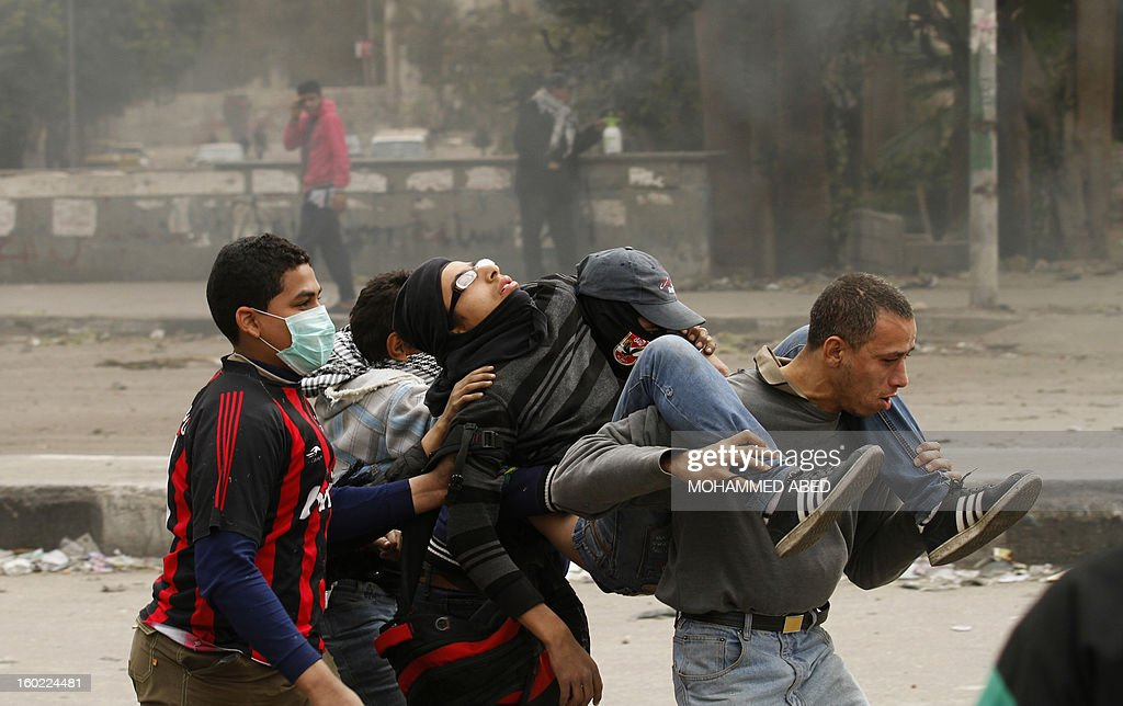 Egyptians protesters carrying a wounded youth during clashes near Cairo's Tahrir Square on January 28, 2013. Egypt's cabinet approved a draft law that would allow President Mohamed Morsi to deploy the armed forces on the streets 'to participate with the police in preserving security and protecting vital establishments.'