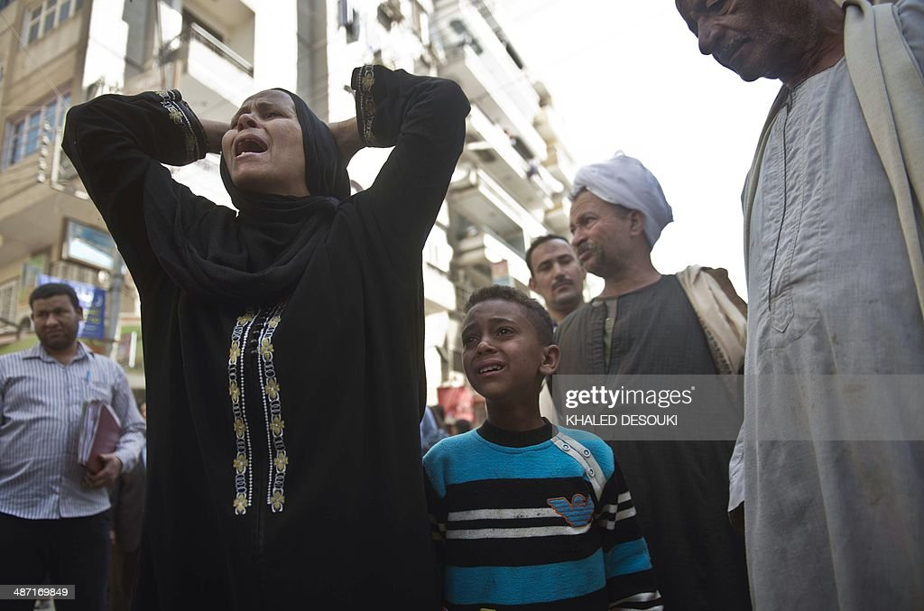 Egyptians react outside the courtroom in Egypt's southern province of Minya after an Egyptian court sentenced Muslim Brotherhood leader Mohamed Badie and other alleged Islamists to death on April 28, 2014. The defendants were accused of involvement in the murder and attempted murder of policemen in Minya province on August 14, the day police killed hundreds of ousted Islamist president Mohamed Morsi's supporters in clashes in Cairo. AFP PHOTO / KHALED DESOUKI