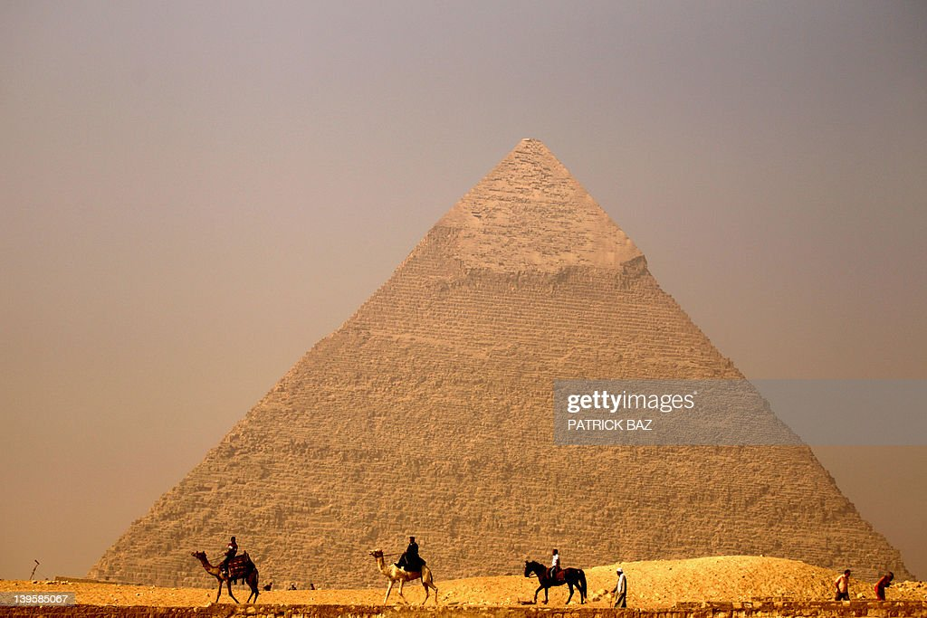 Egyptians ride their camels past the pyramid of Khafre in Giza on the outskirts of Cairo on November 30 2010 AFP PHOTO/PATRICK BAZ