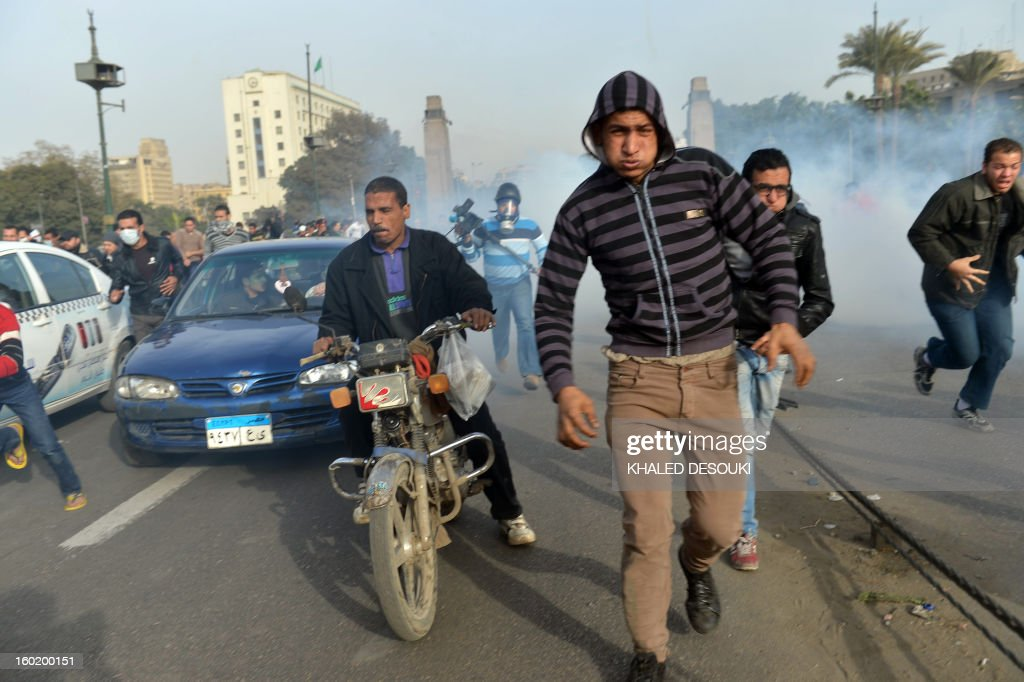 Egyptians run for cover after a tear gas canister is fired by riot police during clashes near Cairo's Tahrir Square, on January 27, 2013. Clashes killed at least 31 people in Egypt's Port Said as violence raged into the early hours in several cities including the capital following death sentences passed on 21 football fans after a riot.