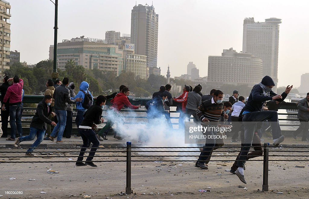 Egyptians run for cover after a tear gas canister is fired by riot police during clashes near Cairo's Tahrir Square on January 27, 2013. Clashes killed at least 31 people in Egypt's Port Said as violence raged into the early hours in several cities including the capital following death sentences passed on 21 football fans after a riot.