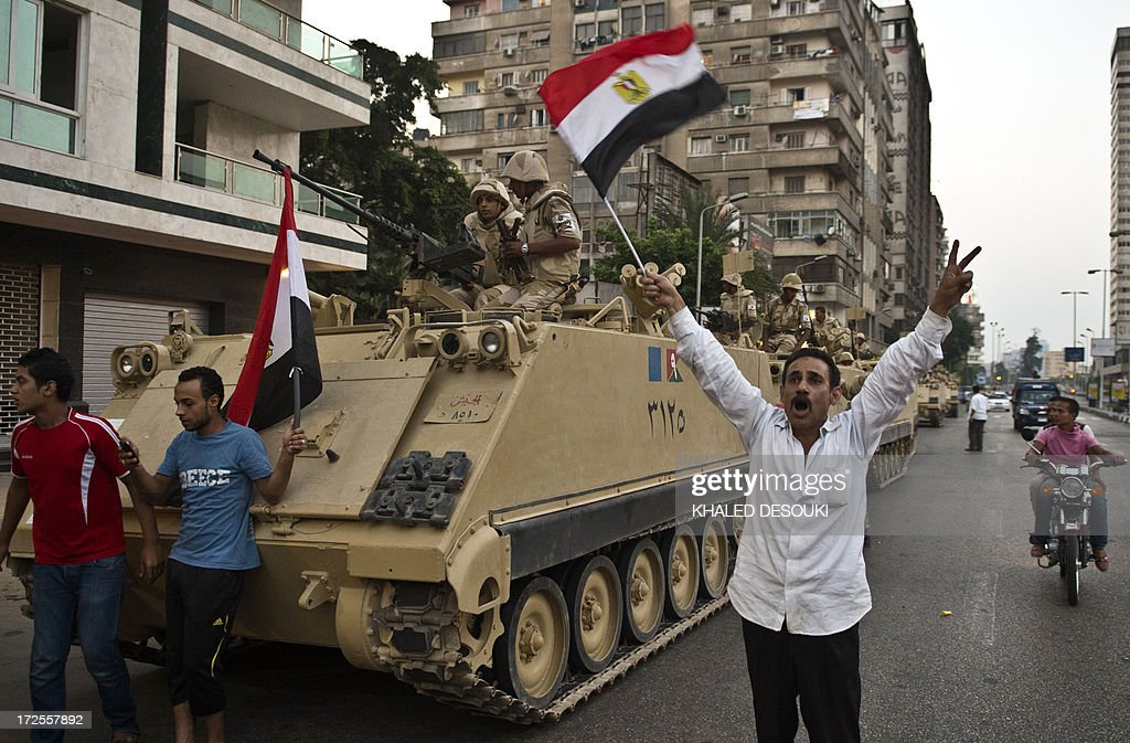Egyptians salute Army tanks upon their deployment on a street leading to Cairo University on July 3 2013 A top aide to Egypt's President Mohamed...