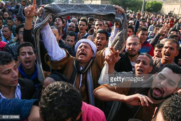 Egyptians shout slogans as they gather outside the the Saint Peter and Saint Paul Coptic Orthodox Church in Cairo's Abbasiya neighbourhood after it...