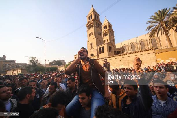 TOPSHOT Egyptians shout slogans as they gather outside the the Saint Peter and Saint Paul Coptic Orthodox Church in Cairo's Abbasiya neighbourhood...