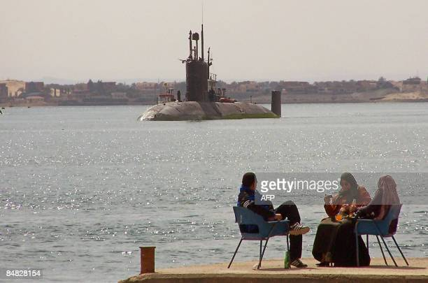 Egyptians sit on a pier as the British Trafalgar class nuclear submarine HMS Trenchant navigates northbound in the Suez canal by the port city of...