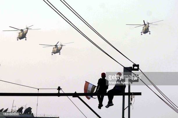 Egyptians sit on top of a lamppost as Egyptian military helicopters fly over Tahrir square during the celebration marking the 40th anniversary of the...