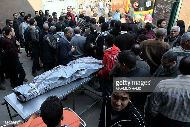 Egyptians stand around the body of a victim of football violence at a morgue in Cairo on February 2 2012 Egypt began three days of mourning after 74...