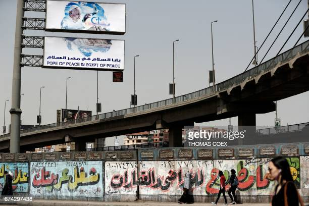 Egyptians walk down a street past graffitied advertisements in the capital Cairo with a billboard seen in the background depicting Pope Francis a few...
