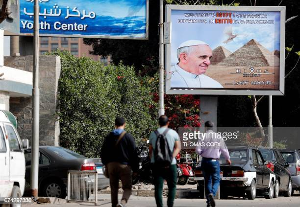 Egyptians walk past a billboard depicting Pope Francis a few hours before his visit commences on April 28 2017 / AFP PHOTO / THOMAS COEX