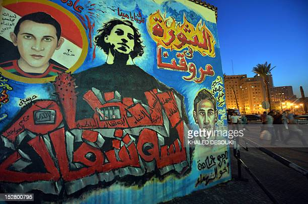 Egyptians walk past a graffiti which reads in Arabic 'Revolution is in our veins' on the wall of Mohamed Mahmud Street in the capital's landmark...