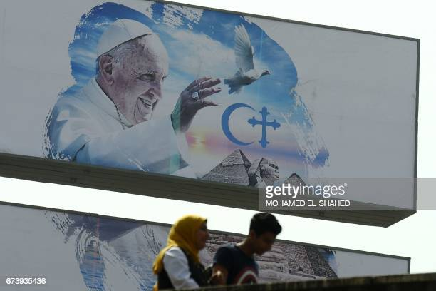 Egyptians walk past a welcome banner bearing a portrait of Pope Francis a day ahead of his visit to the capital Cairo on April 27 2017 Pope Francis...