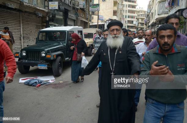 Egyptians walk past blood stains in a street near a church in Alexandria after a bomb blast struck worshippers gathering to celebrate Palm Sunday on...