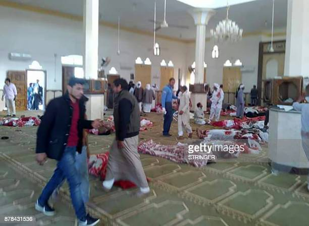 TOPSHOT Egyptians walk past bodies following a gun and bombing attack at the Rawda mosque roughly 40 kilometres west of the North Sinai capital of...