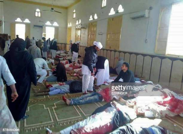 Egyptians walk past bodies following a gun and bombing attack at the Rawda mosque roughly 40 kilometres west of the North Sinai capital of ElArish on...