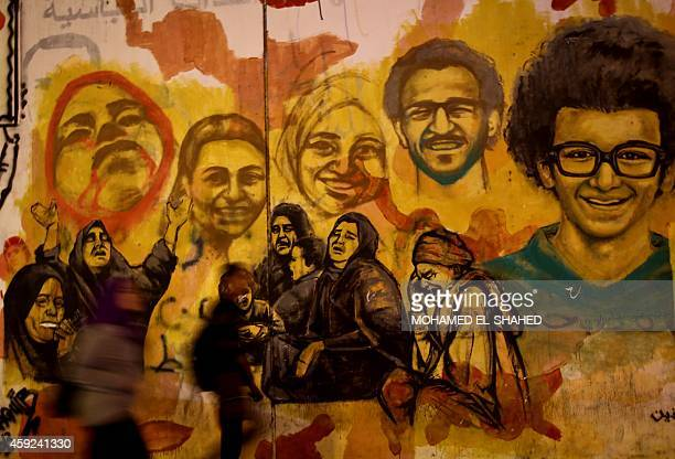 Egyptians walk past graffiti marking the third anniversary of the 2011 protests against the military which ignited deadly clashes with security...