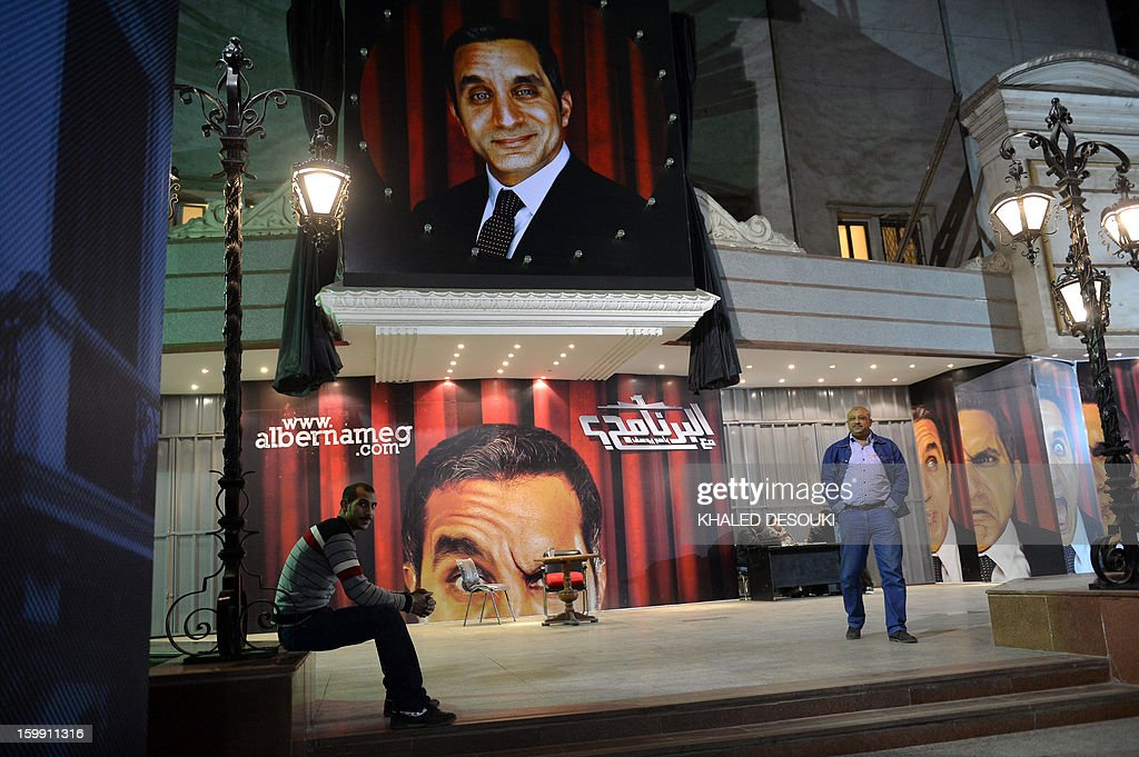 Egyptians walk past posters of Egyptian satirist Bassem Youssef outside a theatre in Cairo on January 22, 2013. The Cairo cafe is packed with patrons in stitches as television host Bassem Youssef fires his caustic criticism at President Mohamed Morsi, but post-revolution media freedoms have proved no laughing matter for some. Youssef, a heart surgeon turned comedian who enjoys a massive following, has now joined the ranks of several colleagues in the media who face charges of insulting the president. AFP PHOTO /KHALED DESOUKI