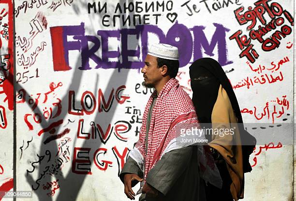 Egyptians walk past revolutionary graffiti on February 13 2011 in Cairo Egypt Two days after the resignation of President Hosni Mubarak the Egyptian...