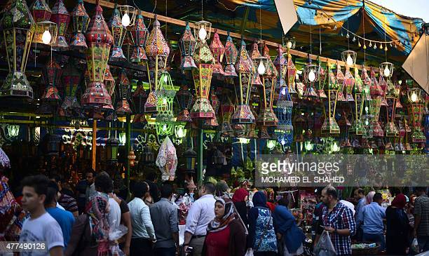 Egyptians walk past traditional lanterns known in Arabic as 'Fanous' sold during the Muslim holy month of Ramadan in the Saida Zeinab district in the...