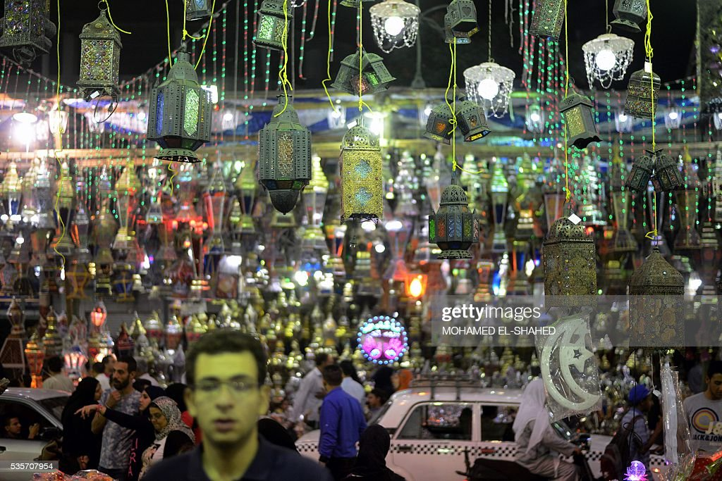 Egyptians walk past traditional lanterns known in Arabic as 'Fanous', sold during the Muslim holy month of Ramadan, in the Saida Zeinab district in the capital Cairo, as the faithful prepare for the start of the holy month, on May 29, 2016. More than 1.5 billion Muslims around the world will mark the holy month which begins this week. Ramadan is the ninth month of the Muslim lunar calendar during which observant Muslims fast from dusk to dawn. / AFP / MOHAMED