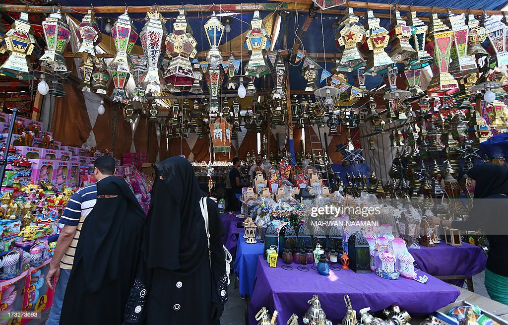 Egyptians walk past traditional Ramadan lanterns displayed at a shop in the working-class Saida Zeinab district in Cairo on the second day of the Muslim holy fasting month of Ramadan July 11, 2013. Many Egyptians are marking Ramadan, where Muslims abstain from eating and drinking from dawn to dusk, as uncertainty riddles the country amid soaring tension following last weeks' toppling of Islamist president Mohamed Morsi.