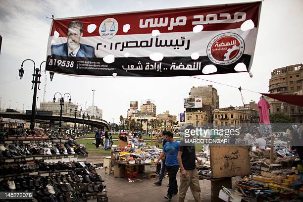 Egyptians walk under a banner of the Muslim Brotherhood's presidential candidate Mohammed Mursi in Cairo on May 25 2012 Egypt looked set for a runoff...