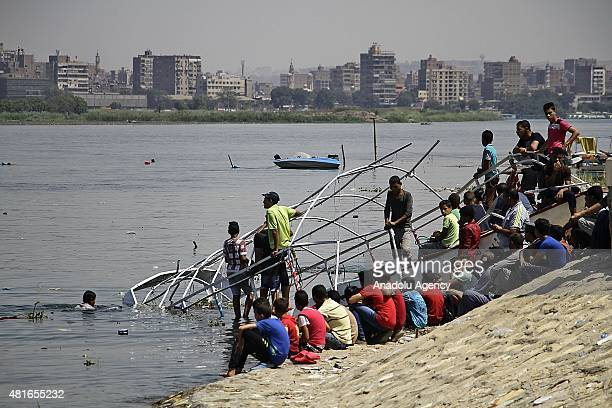 Egyptians watch the search and rescue works after a ferryboat sank in Egypts Nile River late Wednesday on July 23 2015 The ferryboat sank after it...