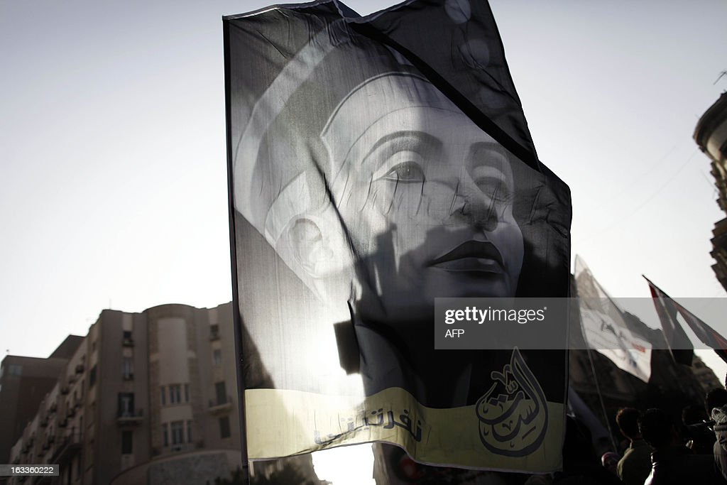 Egyptians wave a flag bearing the portrait of Queen Nefertiti of Egypt, the wife of Pharaoh Akhenaten during the 14th century B.C, as they march in downtown Cairo to mark International Women's Day on March 8, 2013. Faced with a spike in sexual violence against female protesters, Egyptian women are overcoming stigma and recounting painful testimonies to force silent authorities and a reticent society to confront 'sexual terrorism.'