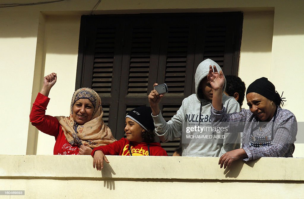 Egyptians wave and take pictures from a balcony as protesters in the street below shout slogans against Egypt's President Mohamed Morsi during a demonstration after Friday prayers in Port Said on February 1, 2013. Thousands of Egyptians flooded the streets in a show of opposition to the Islamist President and his Muslim Brotherhood after a week of a wave of deadly unrest swept the country. AFP PHOTO/MOHAMMED ABED