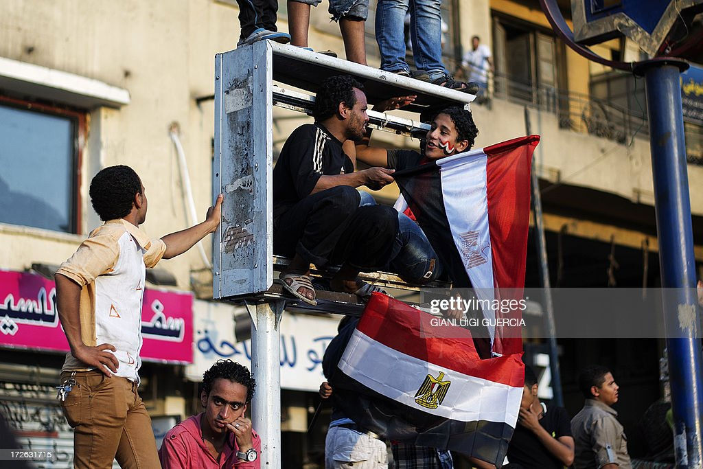 Egyptians wave the national flag atop of a broken advertising sign in Egypt's landmark Tahrir square on July 4, 2013. Egypt's Muslim Brotherhood, from which ousted president Mohamed Morsi hails, denounced a new 'police state' after the arrest of Islamist leaders and the closure of satellite channels. AFP PHOTO/GIANLUIGI GUERCIA