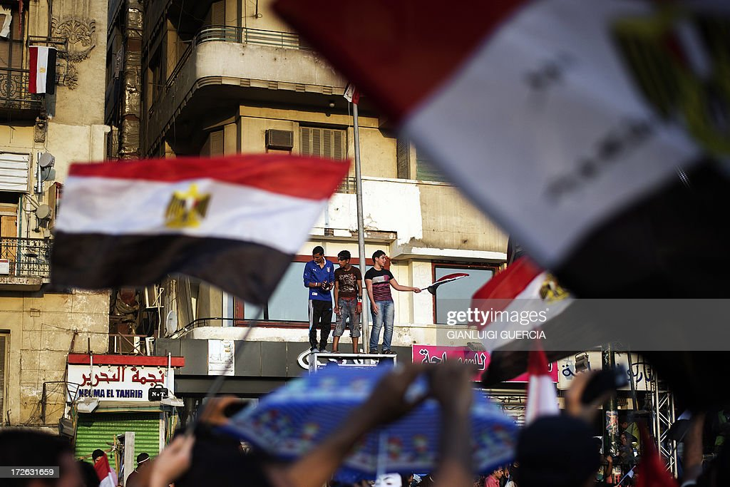 Egyptians wave the national flag atop of a sign in Egypt's landmark Tahrir square on July 4, 2013. Egypt's Muslim Brotherhood, from which ousted president Mohamed Morsi hails, denounced a new 'police state' after the arrest of Islamist leaders and the closure of satellite channels.
