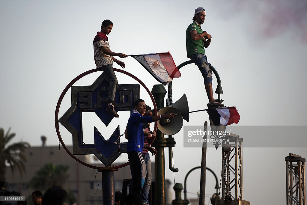 Egyptians wave the national flag atop of the metro sign in Egypt's landmark Tahrir square on July 4, 2013. Egypt's Muslim Brotherhood, from which ousted president Mohamed Morsi hails, denounced a new 'police state' after the arrest of Islamist leaders and the closure of satellite channels. AFP PHOTO/GIANLUIGI GUERCIA