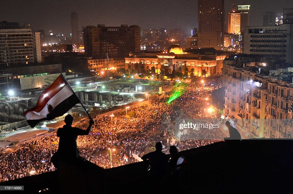 Egyptians wave the national flag on a building rooftop on July 7, 2013 as hundreds of thousands flood Cairo's landmark Tahrir square to demontrate against ousted President Mohamed Morsi and in support of the Egyptian Army. Opponents of Egypt's first freely elected leader packed streets across the country in their hundreds of thousands to show the world his ouster was not a military coup but the reflection of the people's will. Staged two days after Islamist rallies exploded into bloodshed, the protests came as a coalition that backed the military action to overthrow Morsi reportedly agreed to name a technocrat as premier.